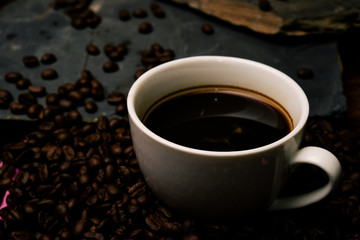 Cup of coffee with smoke and coffee beans on table with coffee beans.