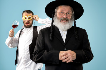 Portrait of old senior orthodox Hasdim Jewish man with kosher wine at Jewish festival of Purim at studio. The purim, jewish, festival, holiday, celebration, judaism, pastry, tradition, cookie