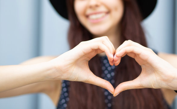 Closeup shot of cheerful girl with long hair making heart shape with her fingers. Space for text