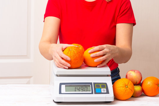 woman weighting fruints on digital weight scales