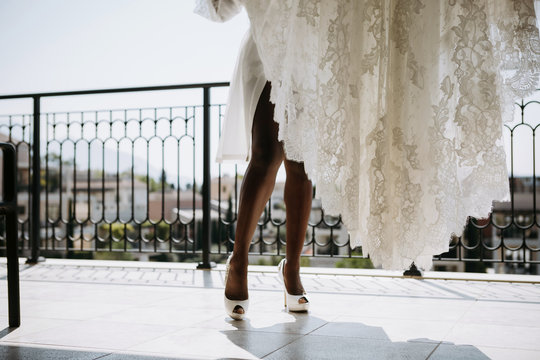 African American bride in fancy shoes stands on the balcony with her dress