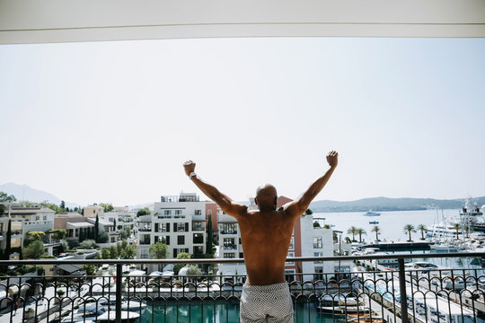African American man stretches standing on the balcony