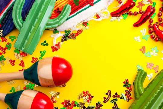 Mexican fiesta and Cinco de Mayo party concept theme with jalapeno pepper necklace, maracas, cactus and traditional rug covered in sombrero shaped confetti on yellow background with copy space