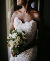 Charming African American bride smiles standing before the window