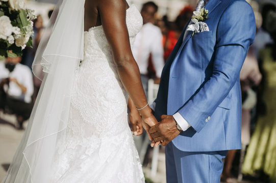 African American newlyweds hold their hands together during the ceremony