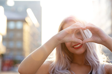 Joyful blonde model with red lips making heart shape with her fingers at the street. Empty space