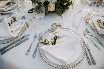 Classic white set of wedding dinner table. White bouquets as a centerpiece