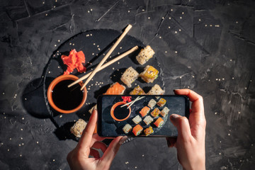 Hands taking photo a different assortment of sushi rolls with smartphone