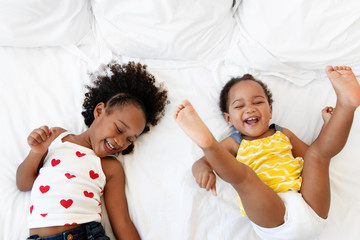 Smiling sisters having fun together on bed