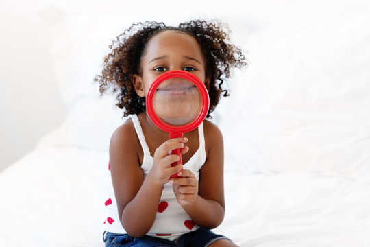 Smiling girl holds magnifying glass