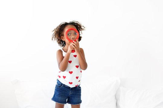 Girl holds magnifying glass over eyes