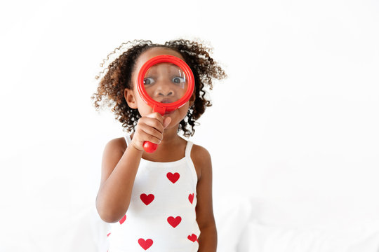 Girl holds magnifying glass over face