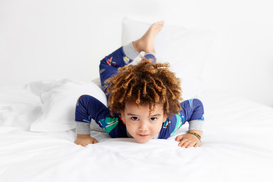 Young boy makes funny pose on bed