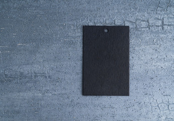 black price tag isolated on decorative textured background. top view