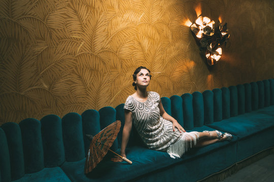 Woman lounges on a velvet bench