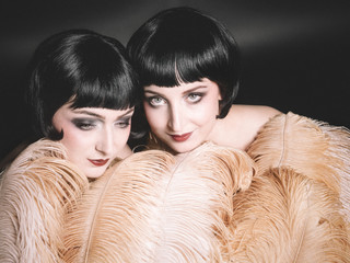 Two women pose behind feathers