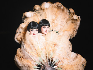 Two women pose behind large feather fans