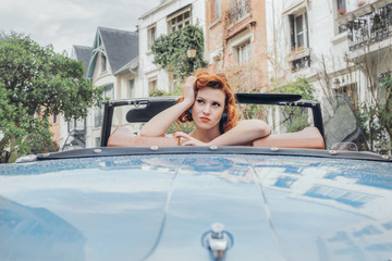 Woman poses in vintage car