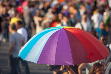 Person holds up a rainbow umbrella