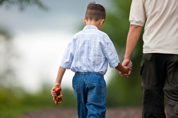 Young boy walking hand in hand with his father.