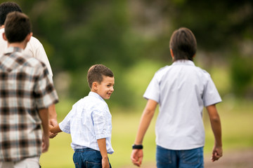 Three boys walking with their father.