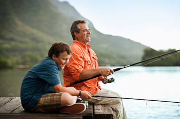 Father and son enjoying fishing together at the lake.
