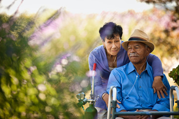 Senior woman hugging her husband with nasal tubes.