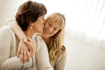 Young woman being kissed on the cheek by her mother.