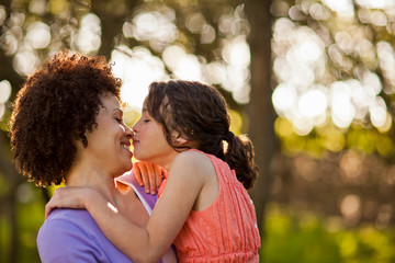Smiling mid adult woman being kissed by her young daughter as she holds her in the forest.