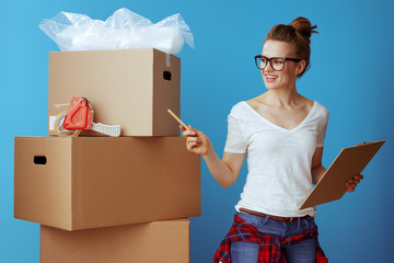 woman near cardboard box using moving checklist and count boxes