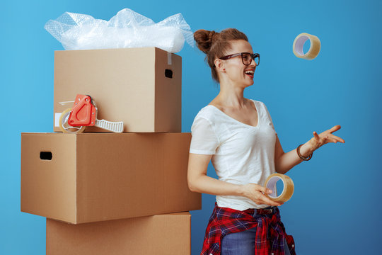 woman near cardboard box throwing up adhesive tapes on blue
