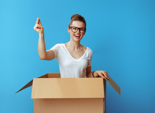 happy woman with fingers snapping in cardboard box on blue