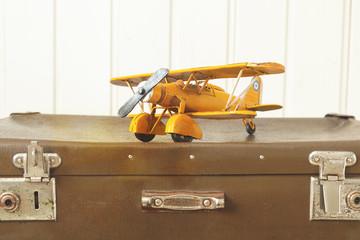 Toy yellow metal plane Old retro suitcases White wooden background Vintage tinting