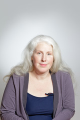 Headshot of an attractive mature woman with beautiful long gray hair in front of white background, copy space.