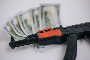 The concept of payment for military operations. Toy gun, the weapon is on cash.