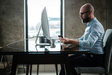 Middle-aged designer paying online in office