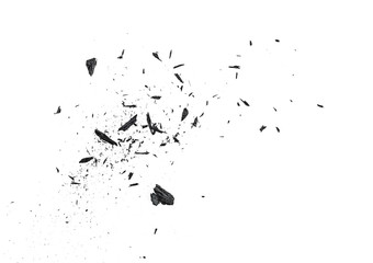 Small pieces of charcoal dust on white background, top view.