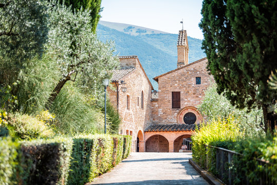 Assisi, Italy town or village city in Umbria with San Damiano church during sunny summer day and road path with nobody