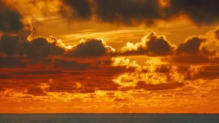Fotobehang - Epic sunrise clouds over orange sky and ocean in Miami, Florida. 4K UHD Timelapse.
