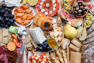 Italian antipasti snacks set. Brushettas, cheese variety, shrimps, salmon, olives, prosciutto with pear, salami and jamon over grey grunge table, top view. Food photography