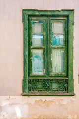 Green wooden vintage window on the old dirty wall