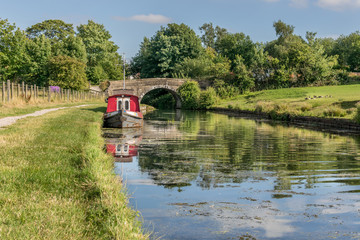 A canal barge moored next to the tow path, near a bridge. Reflections in the water.