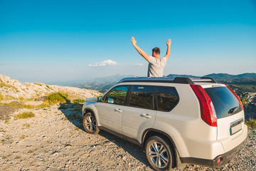 man standing near white suv car on the peak of the hill with beautiful view of mountains