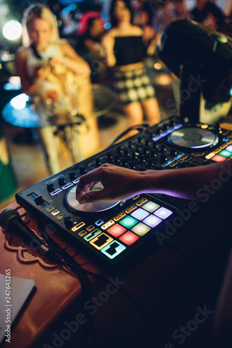 DJ plays live set and mixing music on turntable console at stage in