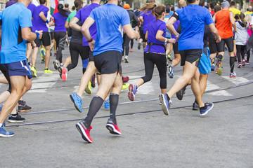 Marathon runners running race people feet on city road