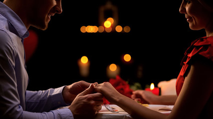 Man holding womans hand, proposing marriage during romantic date, relations