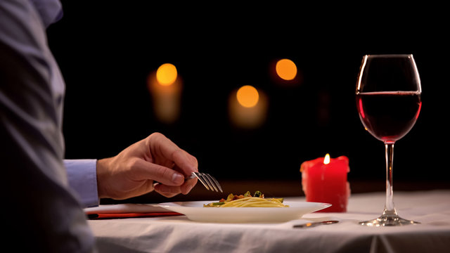 Male enjoying gourmet dinner in restaurant, eating pasta and drinking wine