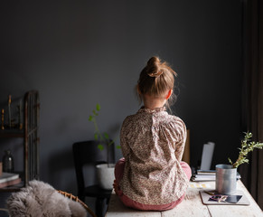 Rear view of girl sitting on table at home