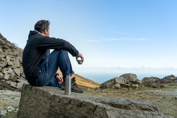 Middle age man sitting on the rock drinking a tea or coffee in cold morning looking on the vale and sea from mountain range, view from behind