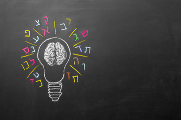bulb with human brain and Hebrew letters chalkboard